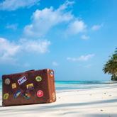 Alter Koffer, beklebt mit Aufklebern verschiedener Reiseziele, steht auf einem Sandstrand mit Palmen