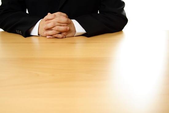 Mann der an einem Tisch sitzt und seine Hände vor sich verschränkt (wobei nur der Oberkörper zu sehen ist)