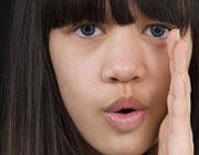 Mädchen hält die Hand an den Mund und formuliert Worte
