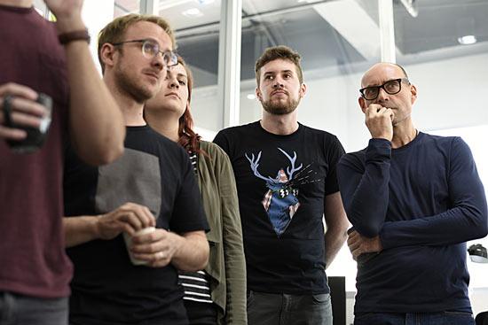Kollegen stehen in einem Meeting zusammen