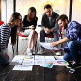 Vier junge Menschen diskutieren ihre Pläne für eine Existenzgründung