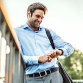 Ein junger Geschäftsmann mit einer Umhängetasche lehnt am Brückengeländer und schaut gut gelaunt auf seine Uhr.