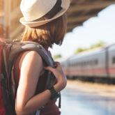 Reisende mit Rucksack wartet auf den Zug an einer Bahnstation