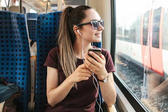 Studentin hört während einer Zugfahrt einen Podcast