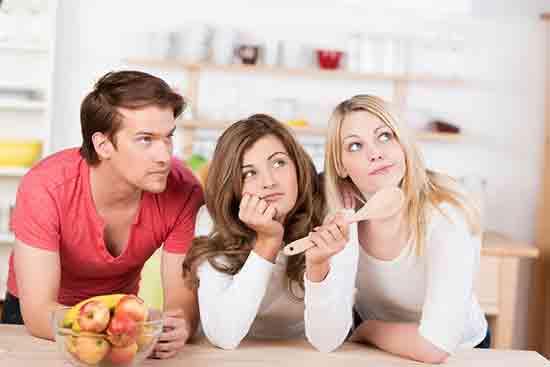 Drei Studenten In Der Küche Mit Kochlöffel
