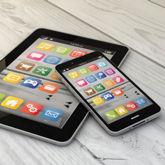 Tablet und Smartphone auf Holzunterlage, diverse App-Symbole auf den Bildschirmen