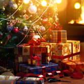 Weihnachtsbaum mit Geschenken davor, im Hintergrund Kamin