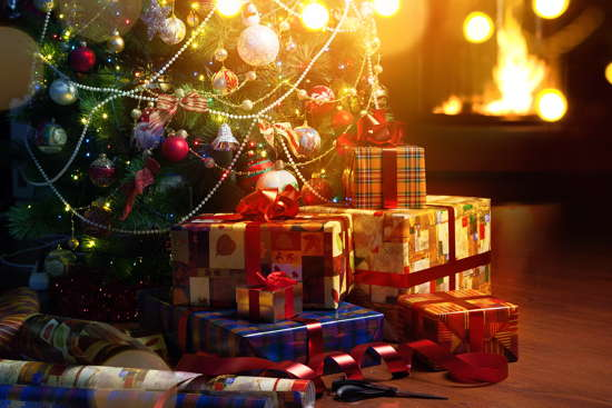 Bunt verpackte Geschenke vor Weihnachtsbaum und Kamin