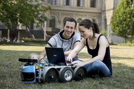 Zwei Studierende mit einem kleinen Roboterfahrzeug auf einer Wiese am Campus der Uni Hannover