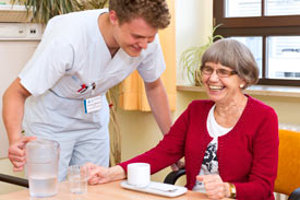 Pfleger lacht mit Seniorin