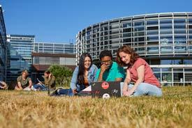 Studierende sitzen auf einer Wiese vor der HS Koblenz