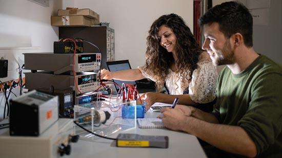 Zwei Studierende mit einem Versuchsaufbau.