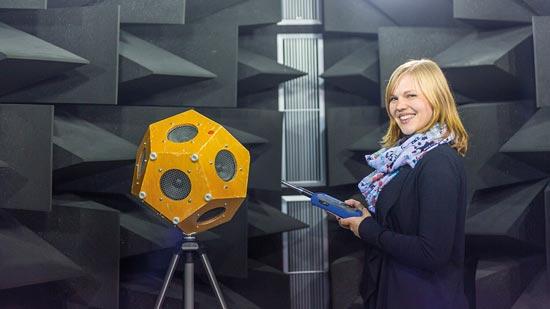 Frau mit Fernbedienung steht neben einem Stativ mit einem Lautsprecherwürfel