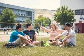 Studierende auf Wiese des Hochschulcampus