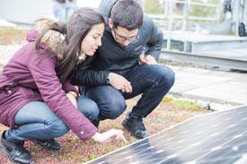 Eine Frau und ein Mann betrachten ein Solar-Panel