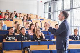 Studenten hören im Hörsaal einem Dozenten zu