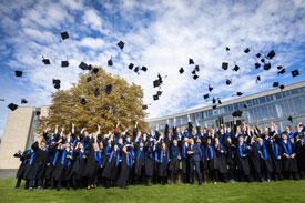 Gruppenbild eines Abschlussjahrgangs: Die Studierenden werfen ihre Hüte in die Luft