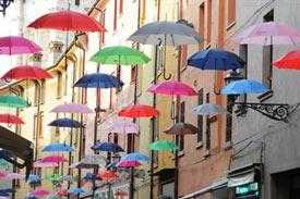 Schirme hängen über einer Gasse in Ferrara
