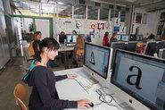 Studierende im Computer-Labor beim Arbeiten mit Schriften (auf mehreren Bildschirmen ist der Buchstabe a in riesiger Auflösung zu sehen)