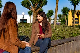 2 Studentinnen sitzen draußen und unterhalten sich