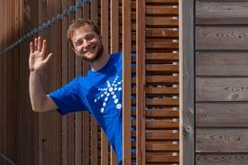 Student in blauem Shirt winkt zwischen Holzpaneelen hervor