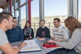 Eine Gruppe Studierender sitzt an einem Tisch in der Caféteria und tauscht sich aus