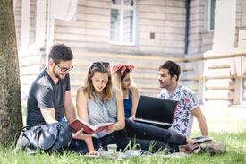 Vier Studentierende sitzen mit Lehrbuch und Laptop im Gras vor der Uni