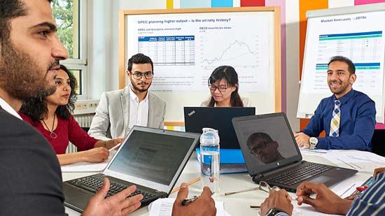 schick angezogene Studierende am Tisch, die etwas besprechen