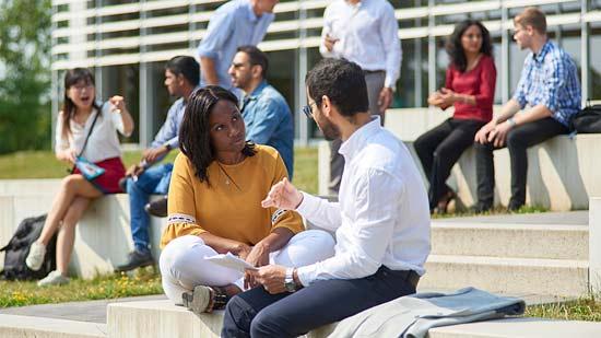 Zwei Studierende unterhalten sich auf dem Campus