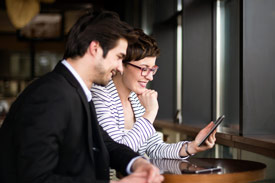 Mann und Frau schauen auf Tablet