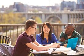 Studierende lernen draußen zusammen.