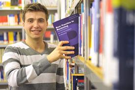 Student zieht Buch aus Regal