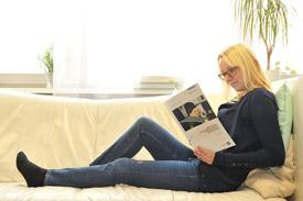Studentin liegt auf Couch und liest.