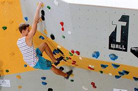 Mann klettert an Wand