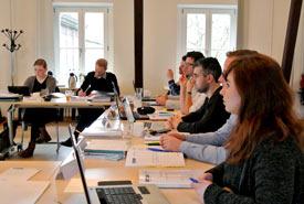 Studierende sitzen mit ihren Laptops an Tischen im Seminarraum