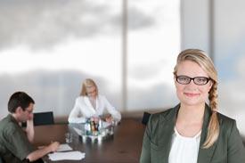 Frau mit Brille vor Konferenztisch, an dem 2 Leute arbeiten