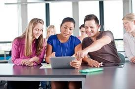 Mehrere Studierende sitzen am Tisch mit einem iPad