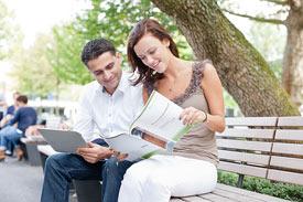 Ein Mann und eine Frau sitzen auf einer Bank und lesen eine Broschüre der Hochschule