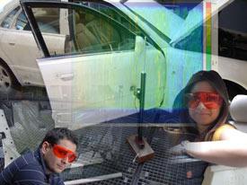 2 Studierende mit Schutzbrillen in Autowerkstatt reingeschnitten