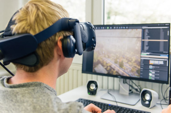 Student mit VR-Brille vor dem Gaming-PC