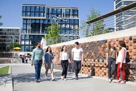 Student/innen laufen vor dem Hochschulgebäude der MSH