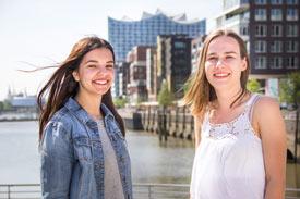 2 Studentiinnen lachen – im Hintergrund Hafencity und Elbphilamonie