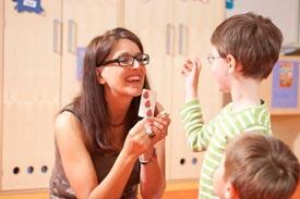 Eine Lehrerin die einem Kind eine Spielkarte zeigt.