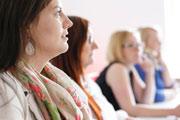 Studentinnen sitzen in einer Reihe an einem Seminartisch