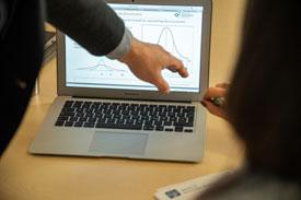 Mann erklärt Kurvendiagramm am PC, Vorlesung