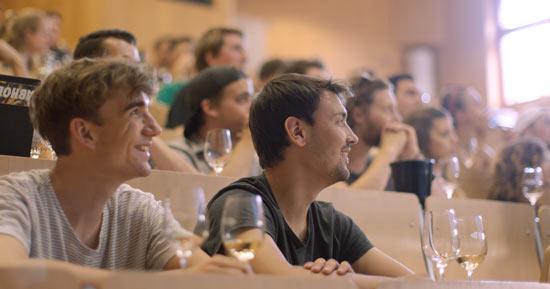 Studierende mit Weingläsern im Hörsaal