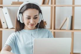 Lernende Studentin mit Kopfhörer und Laptop