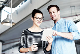 Mann zeigt Frau etwas auf Tablet