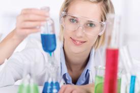 Wissenschaftlerin mit Schutzbrille und Versuchsaufbau