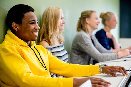 Studierende sitzen an Tischen